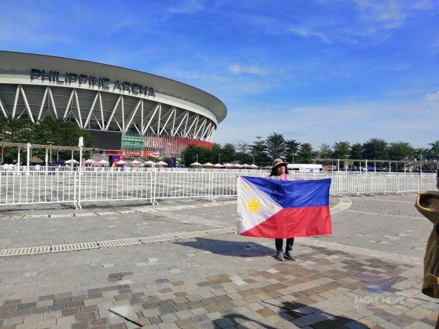 (File photo) A Filipina spectator arriving early at the Philippine Arena, the venue for the historic 30th SEA Games Opening in Ciudad de Victoria, Bocaue, Bulacan, shows her Philippine pride as she poses for a photo with the Philippine flag in front of the 55,000-seater edifice, on Saturday, Nov. 30, 2019. (Photo by Meanne Corvera, Eagle News Service)